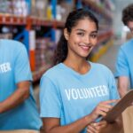 Portrait of smiling volunteer holding clipboard in warehouse